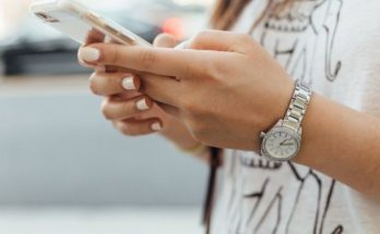 a womens hands holding a cell phone