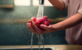 a wmen rinsing fruit in kitchen