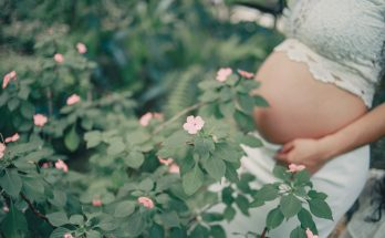 a pregnant women standing near flowers
