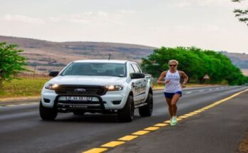 female athlete running besides a motor vehicle