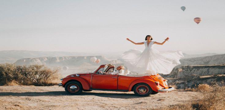 woman-standing-on-volkswagen-beetle